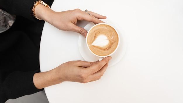 カフェでホットコーヒーとカップを保持している若い女性。女の子は朝、レストランに座っています。女性の手でコーヒーと木製の白いテーブルの平面図です。閉じる。
