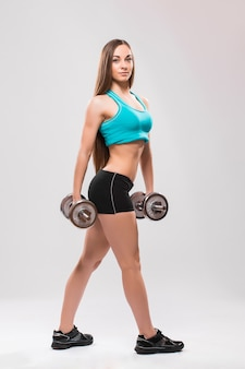 灰色の背景にダンベルを保持している若い女性