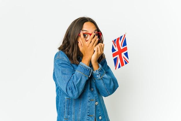 흰 벽에 고립 된 영어 국기를 들고 젊은 여자가 두려워하고 긴장된 손가락을 통해 깜박입니다.