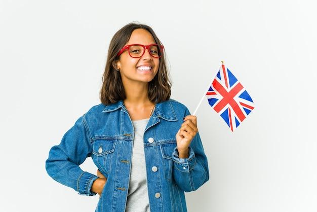 Молодая женщина держит английский флаг на белой стене, уверенно держа руки на бедрах