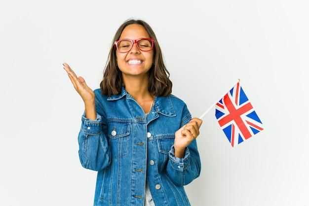많은 웃고 즐거운 흰 벽에 고립 된 영어 국기를 들고 젊은 여자