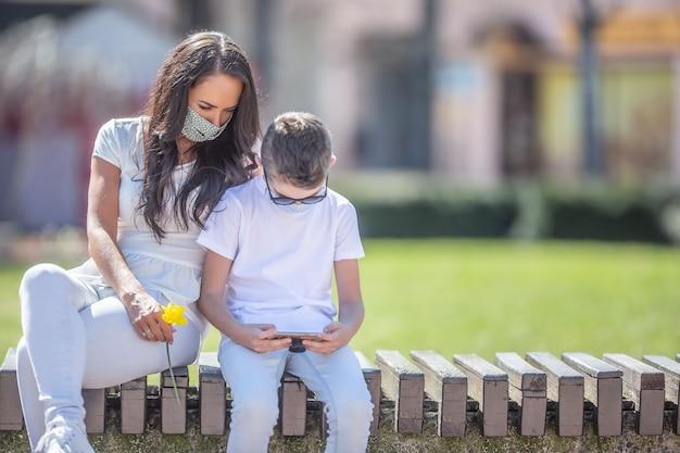 花を持った若い女性が町の男の子の隣に座って、携帯電話を手に見ながらフェイスマスクを着用している。
