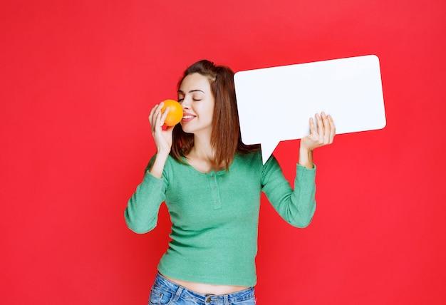 Молодая женщина держит свежий апельсин и прямоугольную информационную доску и нюхает апельсин