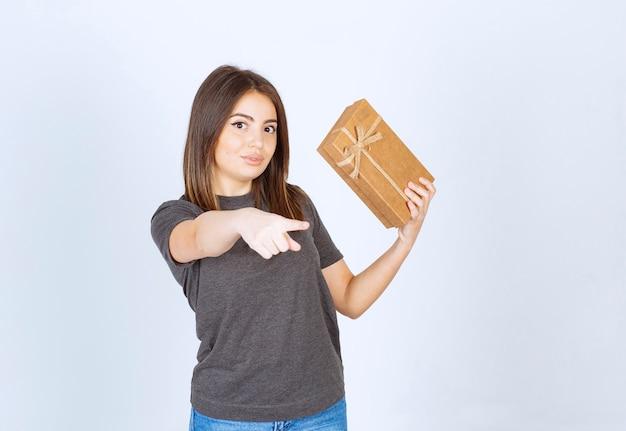 Молодая женщина держит подарочную коробку и указывая на камеру.