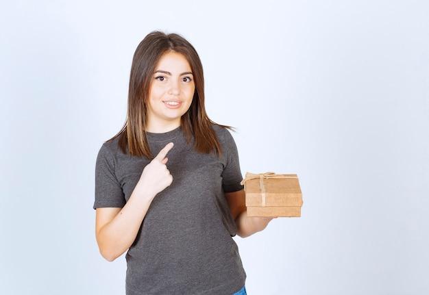Молодая женщина держит подарочную коробку и указывая указательным пальцем.