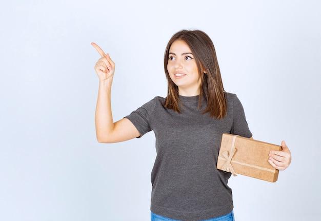 Молодая женщина держит подарочную коробку и указывая вверх.