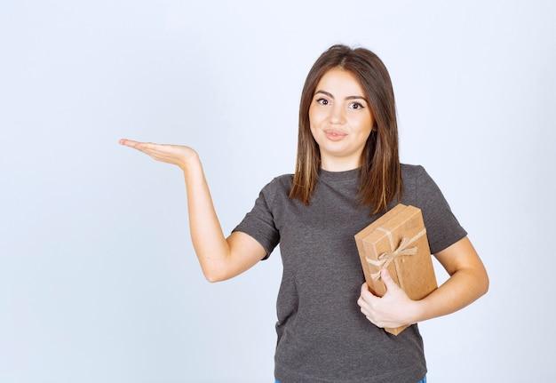 Молодая женщина держит подарочную коробку и показывает руку.