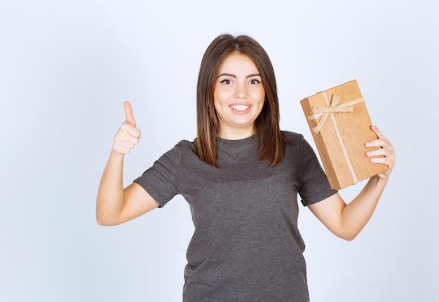Молодая женщина держит подарочную коробку и показывает палец вверх.