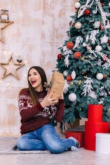 Молодая женщина, держащая подарочную коробку и сидя возле елки.