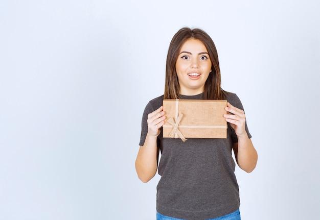 Молодая женщина, держащая подарочную коробку.
