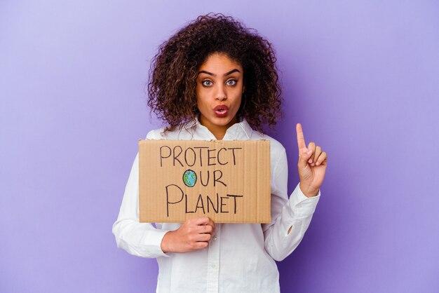 いくつかの素晴らしいアイデアを持っている紫色の壁に分離された女の子のパワープラカードを保持している若い女性。創造性の概念