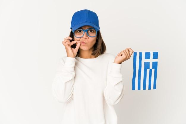 秘密を守る唇に指でギリシャの旗を保持している若い女性