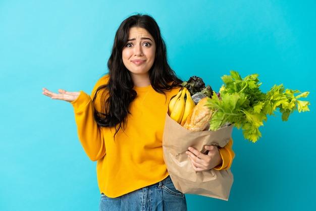손을 올리는 동안 의심을 갖는 파란색 배경에 고립 된 식료품 쇼핑 가방을 들고 젊은 여자