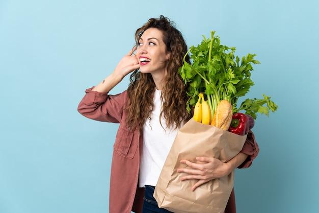 耳に手を置いて何かを聞いて青い背景で隔離の食料品の買い物袋を保持している若い女性