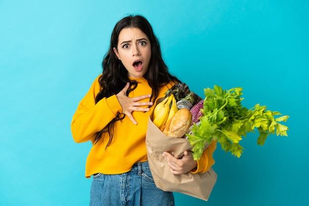 파란색에 고립 된 식료품 쇼핑 가방을 들고 젊은 여자는 오른쪽을 보면서 놀라고 충격