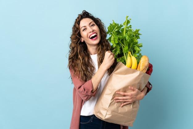 Молодая женщина, держащая продуктовую сумку на синей стене, празднует победу
