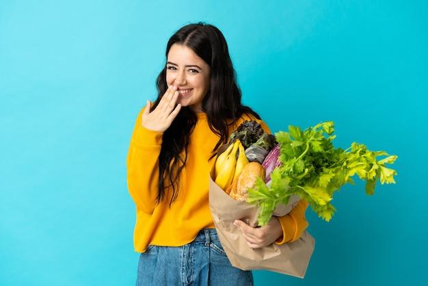 青い壁に分離された食料品の買い物袋を持っている若い女性幸せと笑顔の手で口を覆う