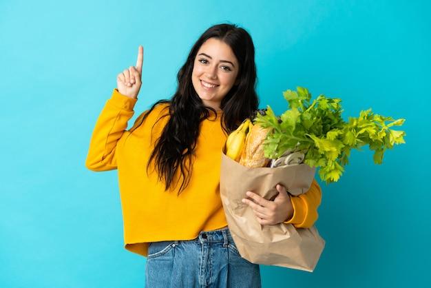파란색 벽에 고립 된 식료품 쇼핑 가방을 들고 젊은 여자가 최고의 기호에 손가락을 들고