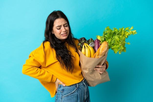 努力したために腰痛に苦しんでいる青い壁に隔離された食料品の買い物袋を保持している若い女性