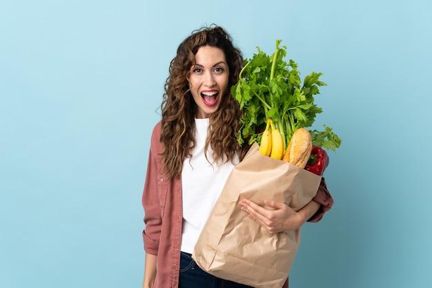 Молодая женщина, держащая продуктовую сумку, изолированную на синей стене с удивленным выражением лица
