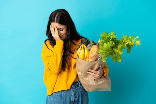 疲れて病気の表情で青い壁に分離された食料品の買い物袋を保持している若い女性