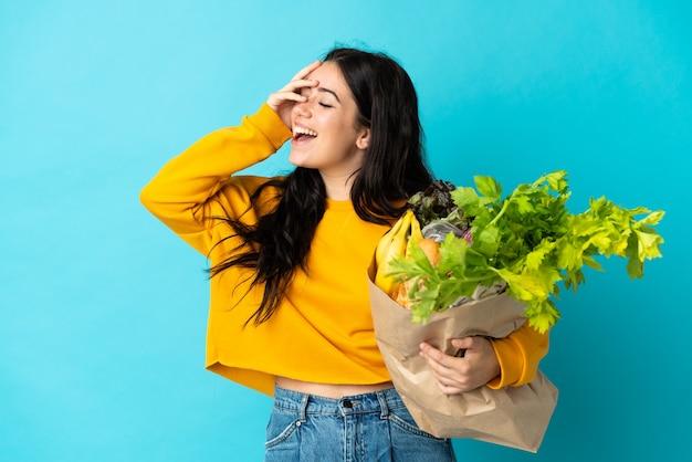 孤立した食料品の買い物袋を保持している若い女性