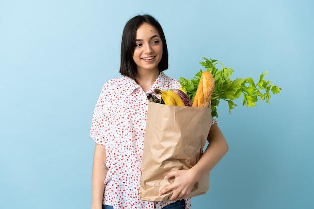 Молодая женщина, держащая продуктовую сумку, смотрит в сторону и улыбается