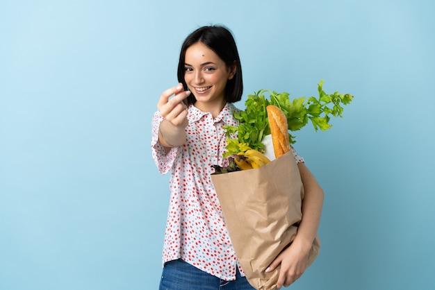 Молодая женщина, держащая продуктовую сумку, делая денежный жест