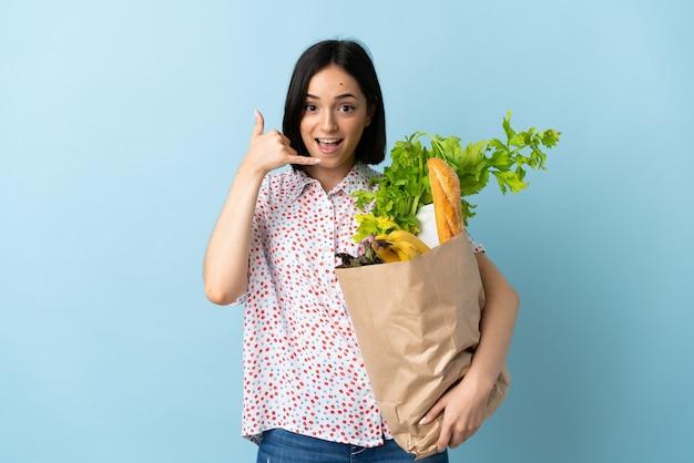 Молодая женщина, держащая продуктовую сумку, делая телефонный жест. перезвони мне знак