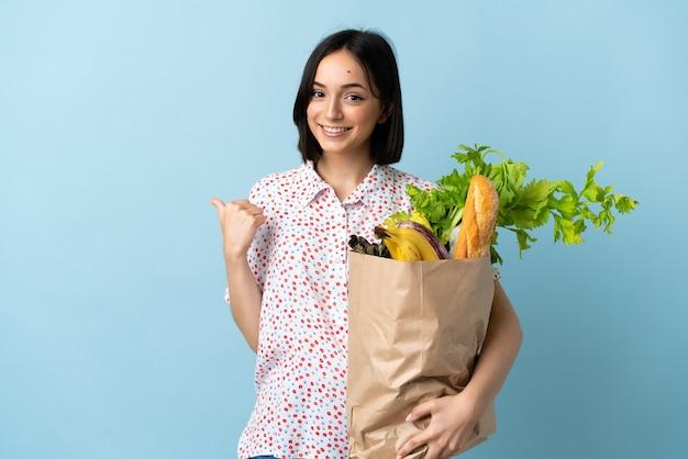 Молодая женщина, держащая продуктовую сумку для покупок, указывая в сторону, чтобы представить продукт