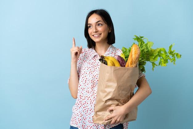 素晴らしいアイデアを指している食料品の買い物袋を持っている若い女性