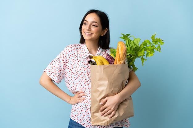 엉덩이에 팔을 포즈와 미소 식료품 쇼핑 가방을 들고 젊은 여자