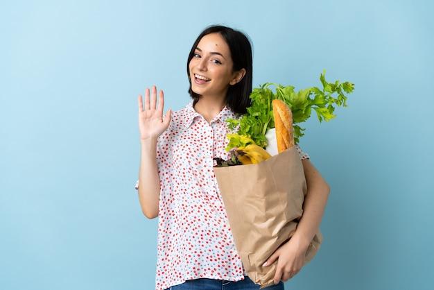 幸せな表情で手で敬礼する食料品の買い物袋を持っている若い女性