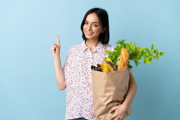 식료품 쇼핑 가방을 들고 최고의 기호에 손가락을 들고 젊은 여자
