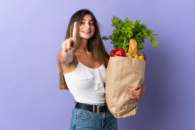 식료품 쇼핑 가방을 들고 손가락을 들고 젊은 여자