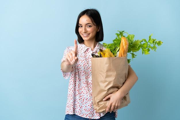 식료품 쇼핑 가방을 들고 손가락을 보여주는 젊은 여자