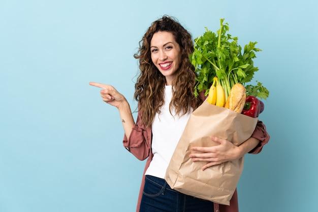 食料品の買い物袋を持っている若い女性
