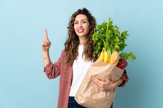 식료품 쇼핑 가방을 들고 젊은 여자