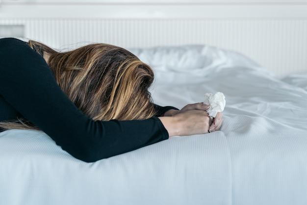 ベッドで彼女の涙を乾かすために使用されるハンカチを保持している若い女性。女性の暴力と虐待の概念、