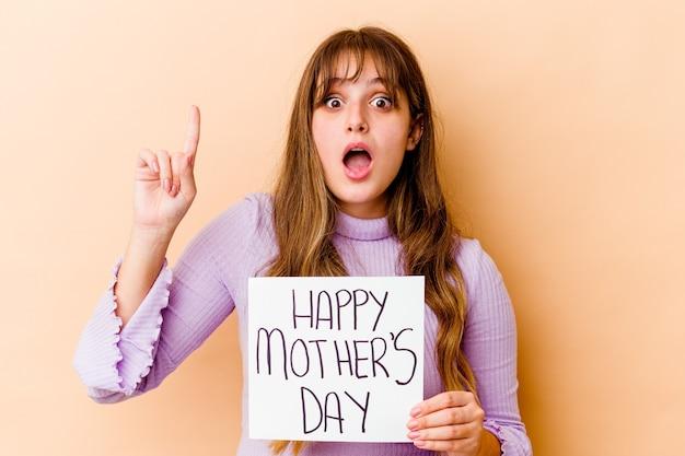 Молодая женщина, держащая плакат дня счастливой матери изолирована с идеей, концепцией вдохновения