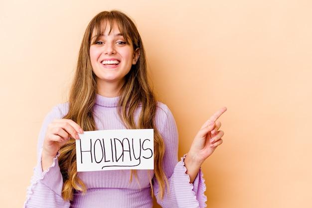 休日のプラカードを持っている若い女性は、笑顔で脇を指して、空白のスペースで何かを見せて孤立しました