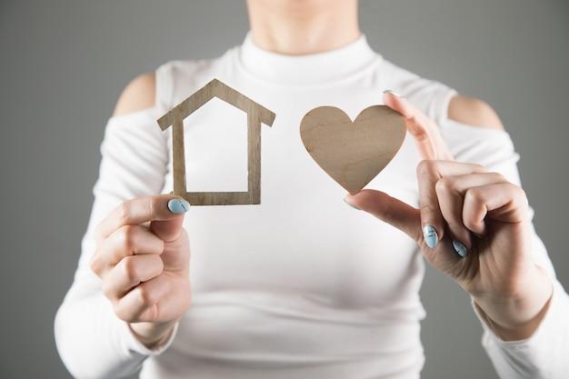 家と心を持っている若い女性。家族の概念