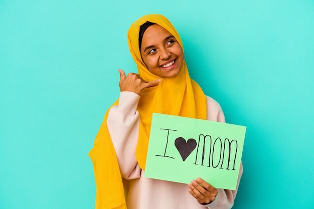 指で携帯電話の呼び出しジェスチャーを示すピンクの壁に分離された私は愛のお母さんを保持している若い女性