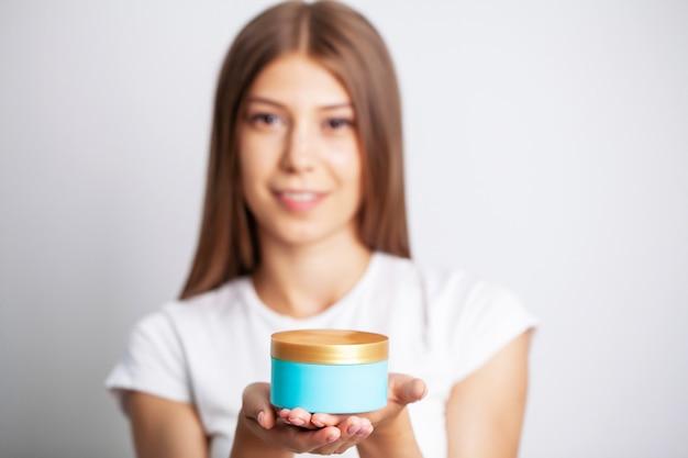 スキンケアクリームの瓶を保持している若い女性