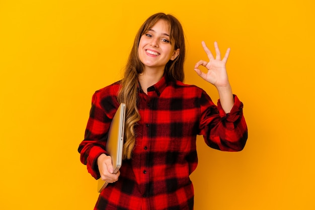 Молодая женщина, держащая ноутбук изолирована, веселая и уверенная, показывая жест ок