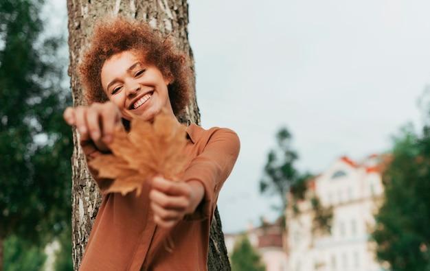 コピースペースを持つ葉を保持している若い女性