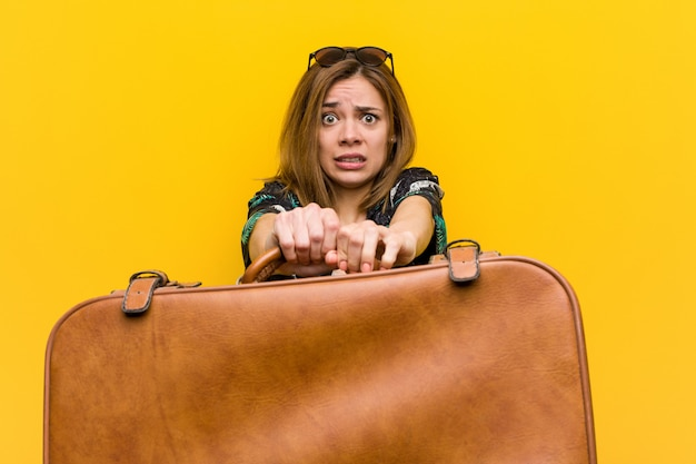 彼女の休暇について怖がっている革のバッグを保持している若い女性、彼女は飛ぶための恐怖を持っています。