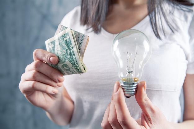 電球とドル札を持った若い女性。コンセプトビジネスアイデア