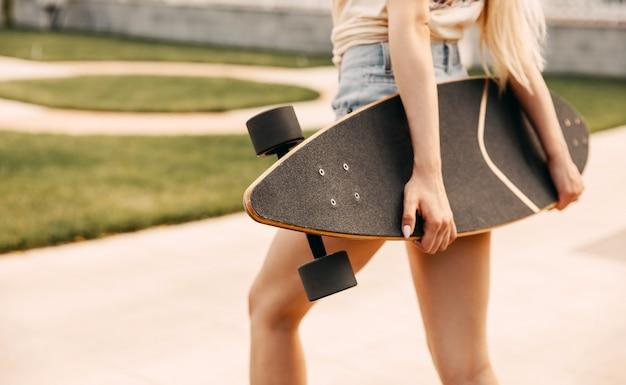 Молодая женщина, держащая лонгборд, на открытом воздухе