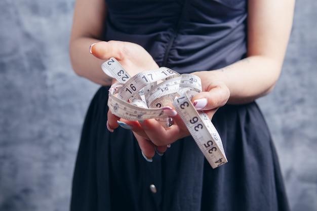 그녀의 손에 측정 테이프를 들고 젊은 여자